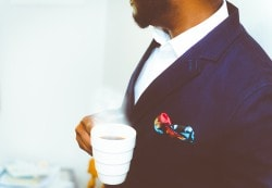 Man in a suit holding a cup of coffee