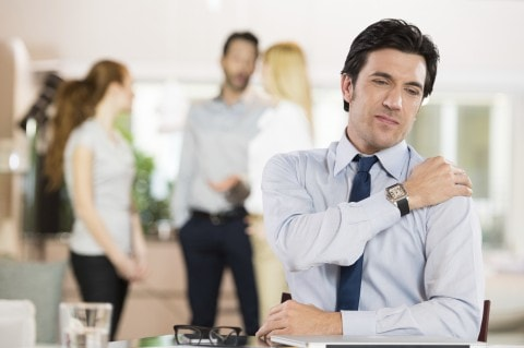 A man holding his shoulder as a sign of stress at work