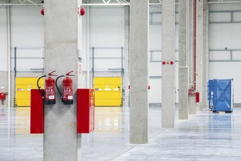 Fire extinguishers on the walls in the huge storehouse